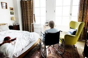 senior loneliness shown with Senior woman sitting on the wheelchair alone