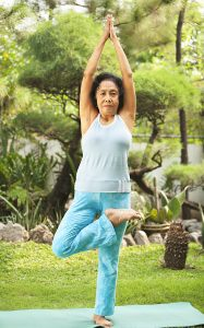 Combatting senior loneliness doing yoga at park in the morning.