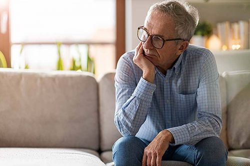 Worried senior man sitting alone in his home. Worried about senior poverty.