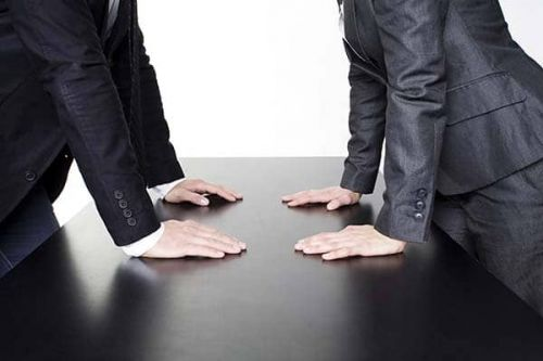 Contesting a Will. Two people staring at each other across the table from one another
