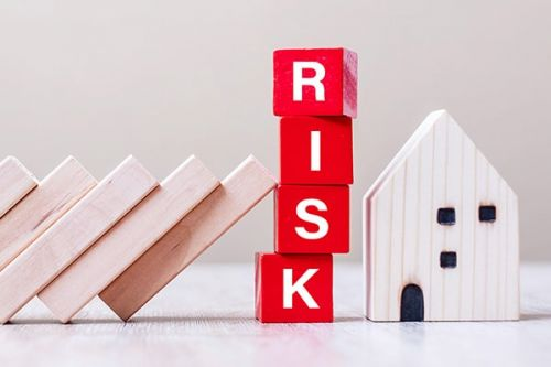 Red RISK cube blocks stop falling blocks protect house showing risk for co-ownership.