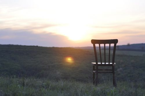 An old antique chair stands on the grass. At sunset. Summer. The concept of loneliness.
