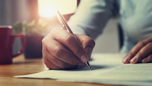 Close up of a person writing a letter of intent.