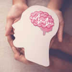 Adult and child hands holding brain paper cut out