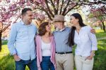 Young couple with senior parents walking outside in spring nature.